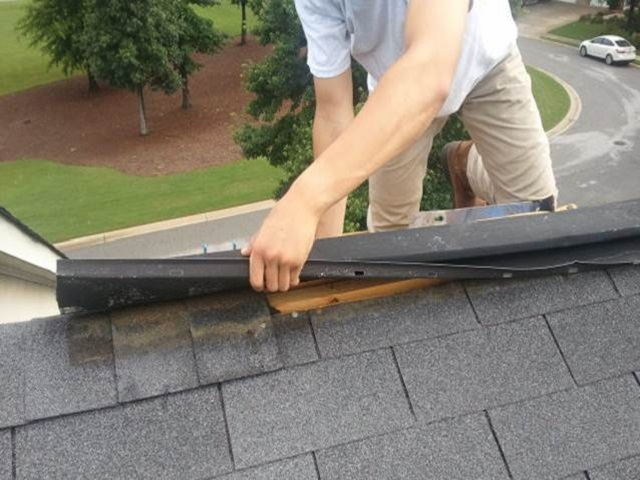 Image of roofer working on loose ridge vents in Manassas Virginia