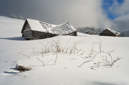Old house in a mountain village. Winter landscape